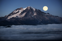 Full moon over mountain covered with clouds