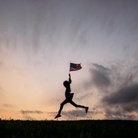 Silhouette girl with American flag running on field against sky