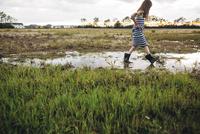 Side view of messy girl walking on wet field 11100042900| 写真素材・ストックフォト・画像・イラスト素材|アマナイメージズ