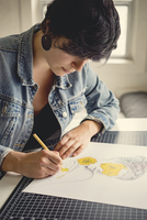 Young female artist drawing on paper
