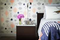 Vase and radio on table by bed against wall in bedroom