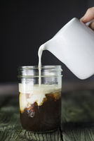 Cropped image of hand pouring milk in coffee drink on table