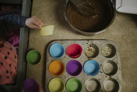 High angle view of girl making cupcakes in kitchen