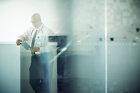 Doctor using tablet computer while standing hospital lobby seen through glass 11100043202| 写真素材・ストックフォト・画像・イラスト素材|アマナイメージズ