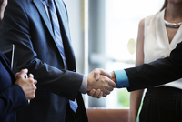 Businessmen shaking hands while standing with colleagues in office