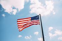 American flag against sky on sunny day 11100043343| 写真素材・ストックフォト・画像・イラスト素材|アマナイメージズ