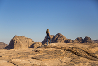 Rear view of woman walking on rocks against clear blue sky 11100043424| 写真素材・ストックフォト・画像・イラスト素材|アマナイメージズ