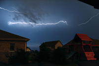 Low angle view of lightning over houses at night