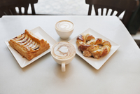 High angle view of cappuccino and pastries on table in cafe