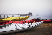 Colorful kayaks moored on shore in foggy weather