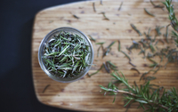 Overhead view of Rosemary leaves in bowl on cutting board