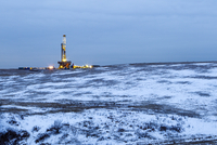 View of oil rig on snow covered land against sky