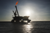 Silhouette oil rig in sea emitting fire