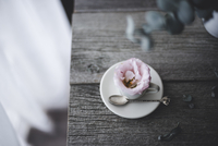 High angle view of flower in coffee cup on wooden table