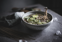 Close-up of soba noodles in bowl with chopsticks on kitchen counter