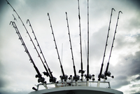 Low angle view of fishing rods on boat against cloudy sky