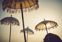 Traditional umbrellas against sky during sunset