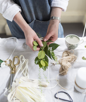 Midsection of woman holding leaves for decorating candle in creative workshop