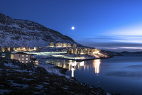 Illuminated buildings by sea against snowcapped mountains