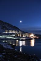 Illuminated buildings by sea against clear blue sky