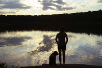 Rear view of woman standing by lake with dog