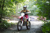 Young female riding motorcycle on dirt road in forest