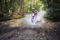 Young female biker riding dirt bike on puddle in forest