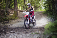 Female biker riding dirt bike on puddle in forest