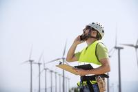 Energy engineer using smart phone at wind farm 11100044316| 写真素材・ストックフォト・画像・イラスト素材|アマナイメージズ
