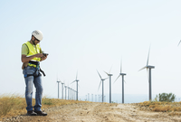 Energy engineer using tablet computer at wind farm against sky 11100044317| 写真素材・ストックフォト・画像・イラスト素材|アマナイメージズ