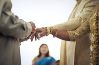 Priest tying fingers of bride and groom during wedding ceremony