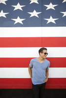 Young man with hands in pockets standing against American flag wearing sunglasses