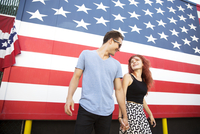 Young couple holding hands while standing against American flag