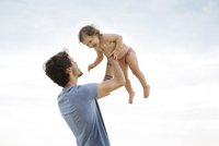Low angle view of father lifting daughter against sky at beach
