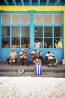 Men playing music while sitting on sidewalk