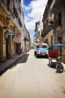 Truck and rickshaw parked on street amidst buildings