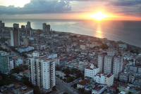 High angle view of cityscape by sea during sunset