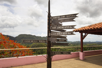 Signboards on observation point by landscape against cloudy sky