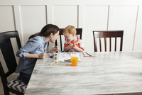 Boy painting with mother while sitting at table 11100044794| 写真素材・ストックフォト・画像・イラスト素材|アマナイメージズ