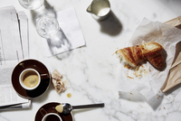 Overhead view of bread and coffee cups on table