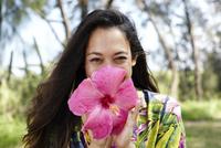 Portrait of happy woman holding hibiscus