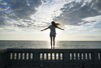 Woman with arms outstretched standing on railing by sea against sky