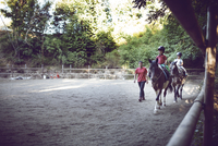 Instructor assisting brothers in riding horse