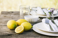 Close-up of lemons by plates on table