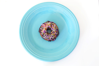 Overhead view of donut with sprinkles in plate