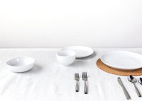 High angle view of crockery and silverware arranged on table against wall