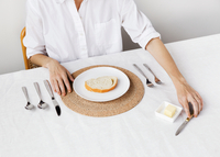 Midsection woman having breakfast at table