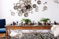 Arranged dining table against decorated wall