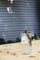 Close-up of lemonade with rosemary on table at yard