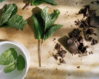 Overhead view of dark chocolate and leaf vegetable on wooden table